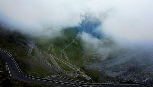 Das Stilfser Joch (2757 m) in den Ortler-Alpen: Nebelschwaden durchziehen die oberen der 48 nummerierten Kehren auf der  Nordost-Flanke; Blick Richtung Stilfs (I, 2016)