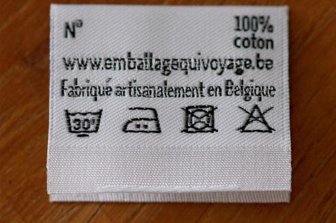 Ceci est une photo du verso de l'étiquette des Emballages qui Voyagent, qui montre notamment les instructions de lavage. A savoir: lavage à 30°C délicat, repassage moyen, pas de séchoir, pas de blanchiment.