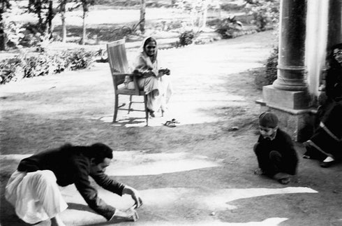 Baba playing marbles with Meherwan. Mansari (right) looking on.