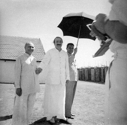 Baba holding Gustadji's hand with Meherjee holding the umbrella