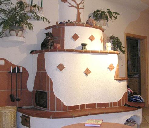 Dieser Kachelofen ist mit Cotto Fliesen verkleidet und hat mehrere Ebenen sowie ein Sichtfenster aus Glas
