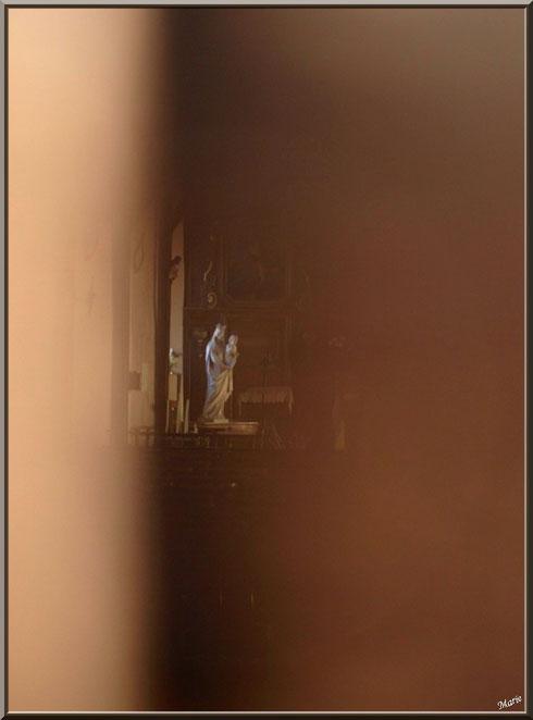 Vierge à l'enfant et, en fond, une partie du rétable à la chapelle Saint-Roch à Saugnacq-et-Muret (40) : vus depuis la fente de la porte d'entrée