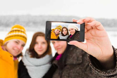 Drei Mädchen, die sich mit einem Smartphone fotografieren