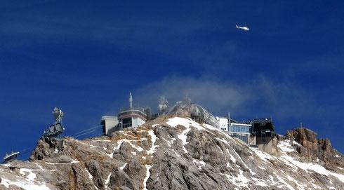 Der überbaute Gipfel der Zugspitze: links die Ehrwaldbahn auf der österreichischen Seite, in der Mitte die Gletscherbahn zum Zugspitzplatt und ganz rechts das Gipfelkreuz. Die Station der Eibsee-Seilbahn befindet sich auf der anderen Seite des Gipfels.