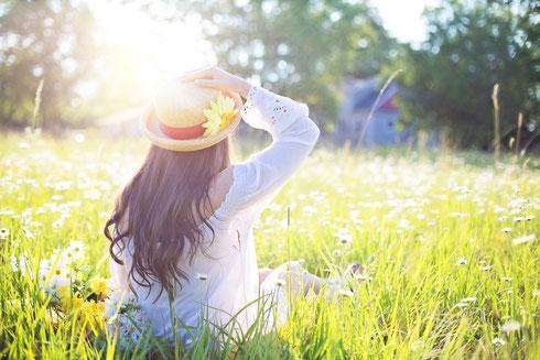 Frau mit Strohhut sitzend auf einer Blumenwiese