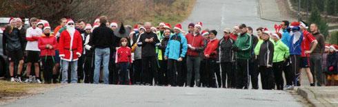 TSV-Präsident Hans-Jürgen Stephan (mit dem Rücken zur Kamera) und Lauf-Organisator Wolfgang Rexhausen (im Weihnachtsmann-Kostüm) begrüßen die Teilnehmer vor dem Start