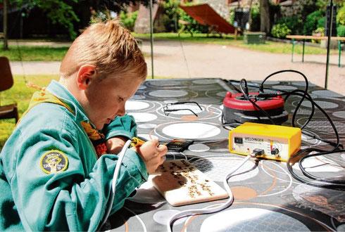 Kreativ mit dem Lötkolben: Mika (l.) schreibt auf Holz, während sich Jonte mit bunten Perlen beschäftigt.