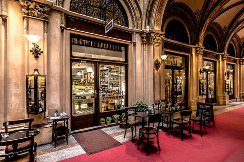Ein elegantes französisches Kaffeehaus in Wien mit einem rotem Teppich vor dem Eingang unter Arkaden im Renaissance-Stil.