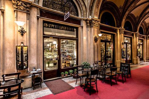An elegant sidewalk café shows its entrance with a red carpet and underneath renaissance arcades.