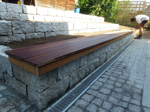 Sitzbank auf Trockenmauer besteht aus Bangkiraiholz