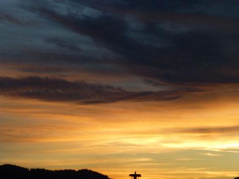 Die Phasen der Trauer annehmen. Hierfür steht das Kreuz vor dem Sonnenuntergang, kurz bevor es Nacht wird.