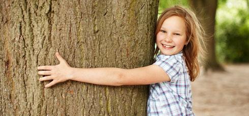 Visionen für Ganztagsschulen. Auf dem Foto ein Mädchen, dass einen Baum umfasst. Visionen für Ganztagsschulen sind die Triebfeder für motiviertes Arbeiten.