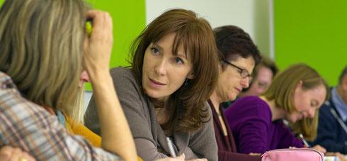 Workshops für Ganztagsschulen bei cbtc. Auf dem Foto Menschen die sich angeregt unterhalten. Für Ganztagsschulen sind Workshops wichtige Orte der Begegnung.