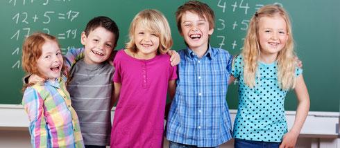 Ganztagsschule. Auf dem Foto stehen lachende Kinder vor einer Tafel. Um im Chaos nicht unterzugehen, hilft cbtc bei der Organisation von Ganztagsschule.