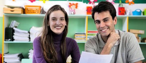 Coaching für Ganztagsschulen. Auf dem Foto ein lachendes Paar, dass gemeinsam lernt. Coaching ist für Leitungskräfte ein wichtiges Element in Ganztagsschulen.