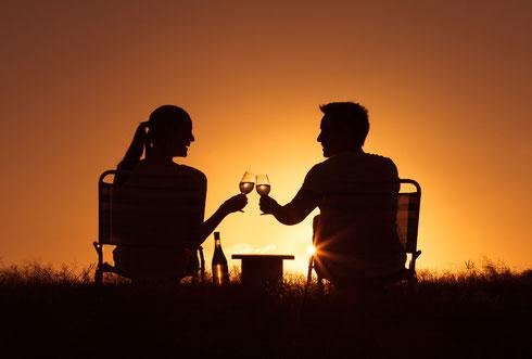 Paar sitzt auf Campingsesseln, beobachten den Sonnenuntergang und stoßen mit Glas Wein an