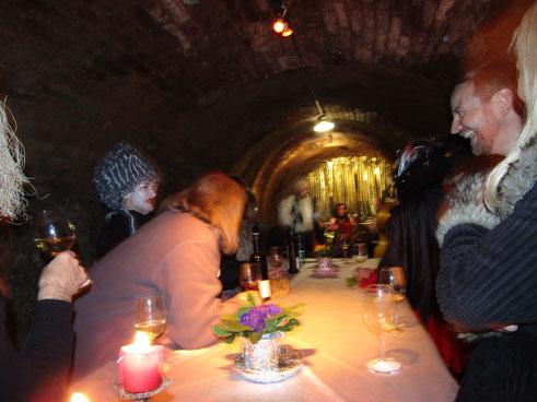 Illustre Gästerunde in einem Weinkeller an einem langen Tisch, im Hintergrund eine Musikgruppe.