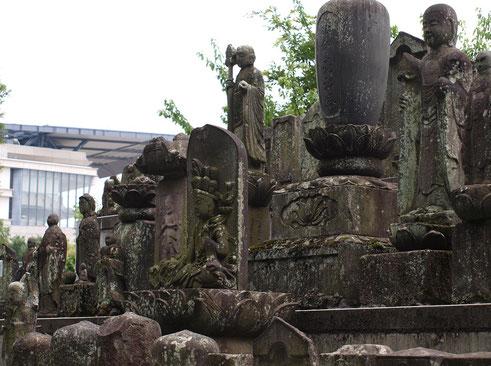 7月26日(2016) 古いものと新しいもの:石仏群とその向こうに見える東京競馬場のスタンド。7月24日、府中市の妙光院境内にて