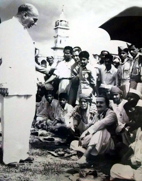 1954 Ahmednagar : Meher Baba having a lunch break from th Dashan programme with Saint Gadge Maharaj sitiing next to him and Sarosh Irani ( standing ) talking to Baba.