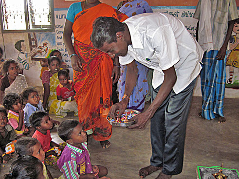 Mr Shakthi, leader of Irular village Chenneri distributes sweets