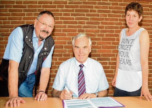 Bürgermeister unterzeichnet Glasfaserverträge.