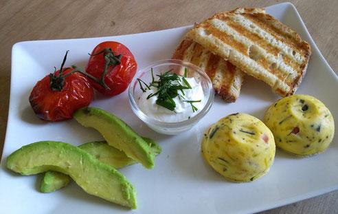 Met geroosterd brood, geroosterde tomaten, avocado en kruidenroom.