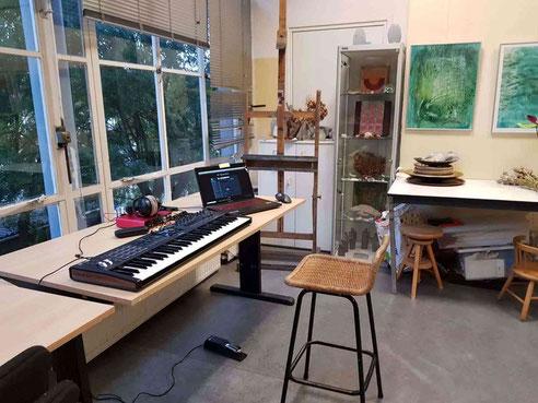 Aan de linkerkant zijn de grote ramen van het atelier, met daar achter twee grote , nu groene bomen, Op de tafel staan de instrumenten van Toff, rechts een vitrine kastje en een paar schilderijen