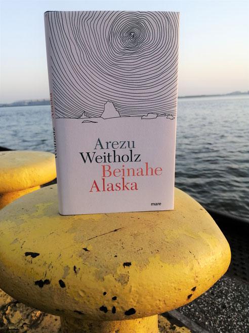 Foto von Buch auf Poller am Meer