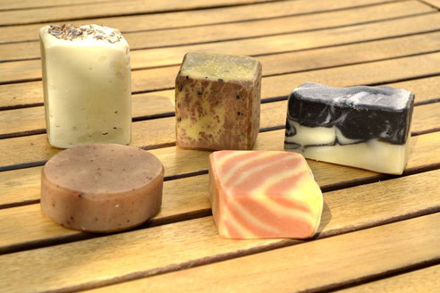 Im Uhrzeigesinn: Lavendelseife, Seife des roten Drachen (mit schwarzem Sesam), Black & White Seife, katalanische Seife (mit roten und gelben Streifen), runde Gewürzseife (schwarzer Pfeffer, Ylang-ylang, Nelke).