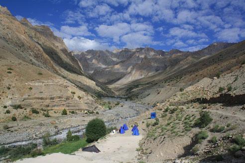 Schotterbett mit Fluss, fünf blaue Zelte, viel Landschaft und Himmel mit Schäfchenwolken.