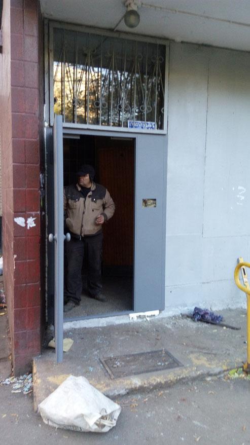 Металлическая дверь в многоквартирный дом со стеклом.