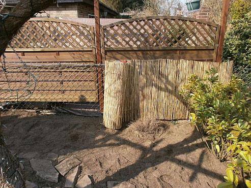 Eine Strohmatte lässt den Gartenzaun verschwinden und bildet nun die Rückwand