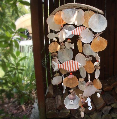 Klangspiel in orange mit Muscheln und Fischen.