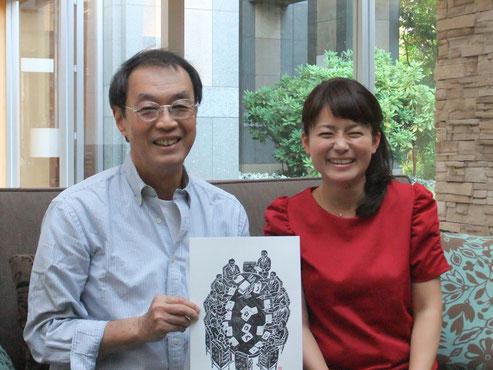 右が、NHK『ひるまえほっと』レポーターの松尾衣里子さん。原田が手に持っているのは、当時のピクトグラムの開発風景を版画にしたもの。松尾さんの、明るいながらも配慮の行きとどいたお人がらもあって、とても楽しい打ち合わせとなりました。(2014年9月30日、白金台の原田工房にて)