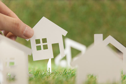 紙でできた家を指でつまみ上げている