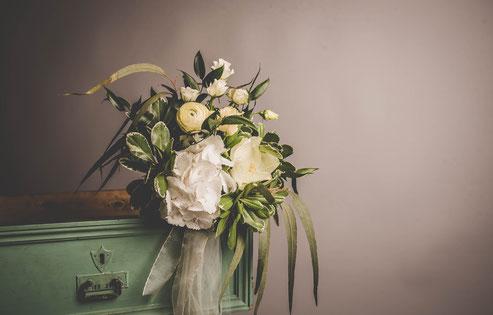 composition florale désuette et romantique de couleur verte et blanche sur commode ancienne. roses blanches en bouton et pittosporum bicolore vert et crème. nezignan l'évêque pezenas hérault occitanie france.