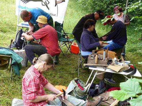Workshopteilnehmer dengeln ihre Sensenblätter. Foto: Clemens Hackenberg