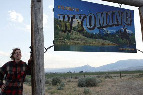 Bloggerin am Schild des Staates Wyoming