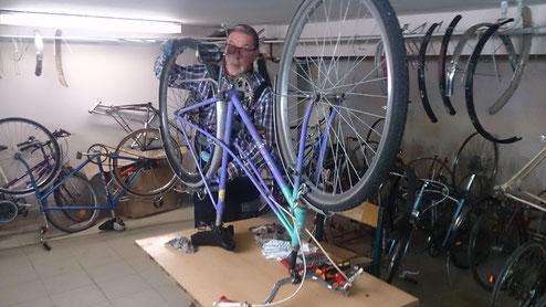 Helmut bei der Fahrradreparatur. Einige Reparaturen oder defekte Räder sieht man im Hintergrund