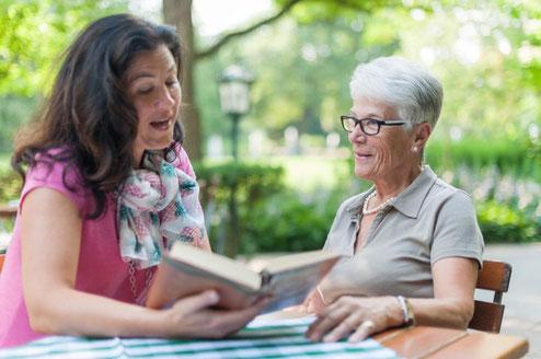 Senioren-Assistentin liest einer Seniorin vor.