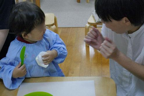 1歳児が、もち粉と豆腐の入った生地を指でつかんで、こねています。