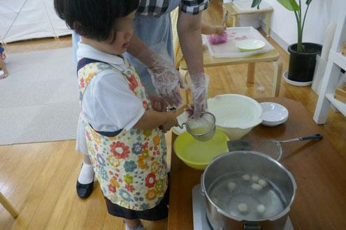 幼稚園児クラスの団子づくりで、お湯を使って、まるめた団子を湯がきました。湯気が熱いので注意しながら行っています。