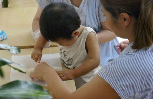 モンテッソーリ活動の団子クッキングで、1歳児が生地をナイフで切っています。