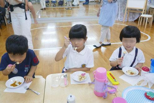 幼稚園児が自分で作った月見団子を、きな粉と黒蜜をたっぷりかけて試食しています。