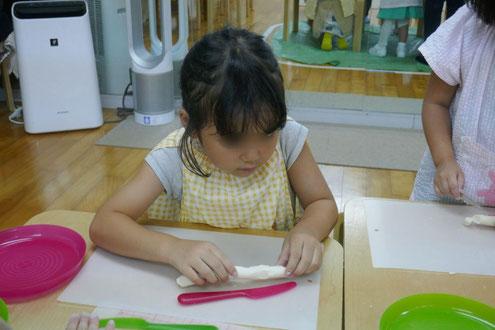 幼稚園児がモンテッソーリの活動で月見団子づくりに挑戦。こねた生地が15cmになったかどうか、ナイフと長さを比べながら確認しています。