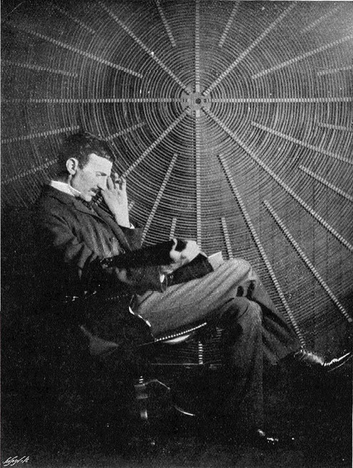 "Nikola Tesla, with Maxwell's book ""scientific papers"", in front of the spiral coil of his high-frequency transformer at East Houston St. 46, New York (Not really Roger Boskovich's book, ""Theoria Philosophiae Naturalis"")"