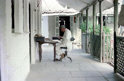 Feram translating documents for Lord Meher ; photo taken by David Fenster
