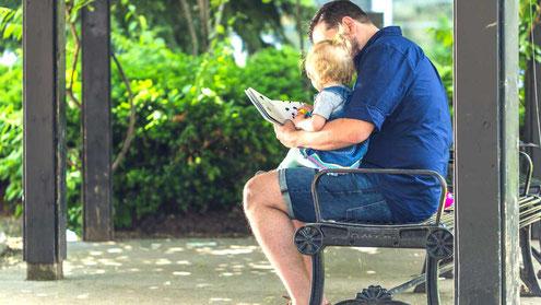 子供を膝にのせて本を読み聞かせる父親