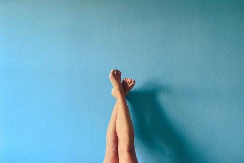 Frauenbeine hochgesteckt vor blauer Wand