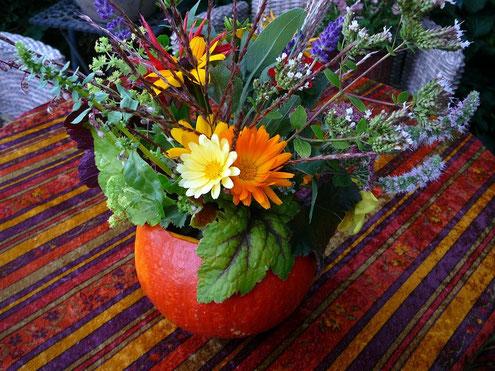 Herbstbüten und Gräser im ausgehöhlten Hokkaido- Kürbis